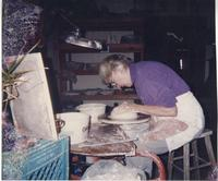 Woman working clay on pottery wheel
