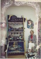 Woman beside decorative shelves and pottery