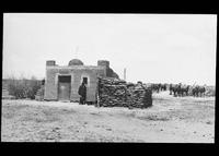 Man in front of adobe house