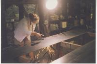 Woman in studio cutting gate top