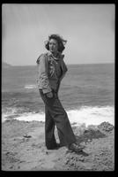 Woman in military jacket and pants, sand beach