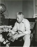 Manuel Mello sitting in his home holding his cornet