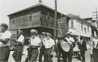 Members of the George Williams Brass Band playing and marching during a parade