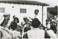 Young boy dancing atop a table amongst a crowd of Women and children