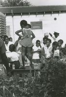 A young girl and boy dancing on top of a table amongst a crowd of Women and children