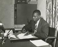 Alton Purnell writing at a desk