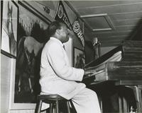 Snookum Russell playing the piano in a nightclub