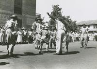Men and children of the George Williams Brass Band dancing during the YMOBA Jr. Division parade
