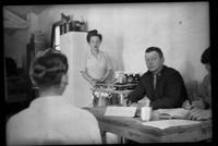 Two nurses, military medical officer at desk with books