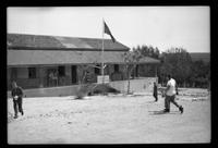 View of camp headquarters with flag and people walking by
