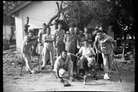 Group portrait of patients with crutches and wheelchair outside in front of building