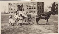 Women and children with a horse-drawn buggy