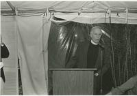 Man at a podium in a tent