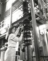Woman putting a chemical on metal machinery