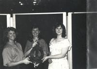 Three women holding an object with greek letters on it